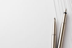 Pens and Blank Papers on Top of White Table. Close up Silver Pens and Blank Bond Papers on Top of White Table with Copy Space on the Left Side royalty free stock image