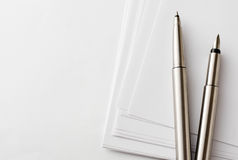 Pens and Blank Papers on Top of White Table Royalty Free Stock Photo
