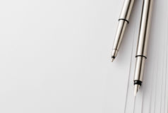 Pens and Blank Papers on Top of White Table Royalty Free Stock Image