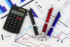 Pens and calculator on financial chart Stock Image