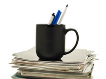 Pens in a coffee mug atop stack of magazines. A black mug holds three pens atop a stack of magazines royalty free stock image