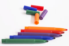 Pens. Colored pens and their colored caps royalty free stock photography