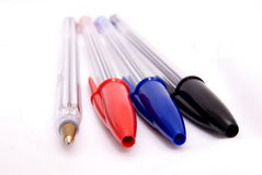 Pens of different colours. Four pens and one without a lid showing the ballpoint Stock Image