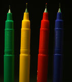 Pens - four colours. 4 coloured pens stand on black background royalty free stock photography