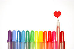 Pens and heart. Rainbow colors pens and heart mark drawn with a red pen on a white background Stock Images