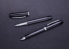 Pens lying on black leather background with copy space Stock Photography