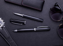 Pens lying on black leather background with copy space Royalty Free Stock Photo