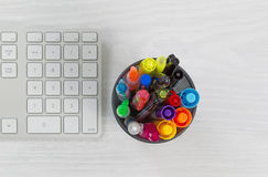 Pens and markers in container on top of desk Stock Images