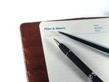 Pens on a memo agenda. Pens and agenda for business men Stock Image