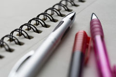 Pens on notepad. Closeup detail. Royalty Free Stock Photo