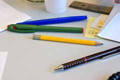 Pens & Pencils. Pens and pencils, over a working desk Stock Images