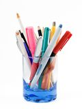 Pens and pencils. Colourful pens and pencils in a blue glass isolated on a white background royalty free stock images
