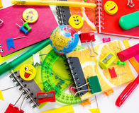 Pens, pencils, erasers, with smileys and a set of notebooks. Royalty Free Stock Photography