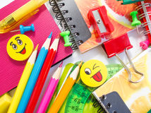Pens, pencils, erasers, with smileys and a set of notebooks. Royalty Free Stock Images