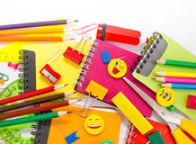 Pens, pencils, erasers, with smileys and a set of notebooks. Stock Photos