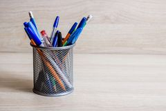 Pens and pencils in metal stand. On a wooden background royalty free stock image