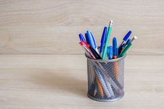 Pens and pencils in metal stand. On a wooden background stock photo