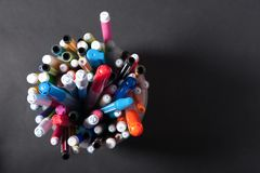 Pens pens pencils. In a plastic jar on a dark background royalty free stock photo