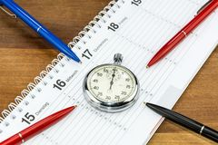 Pens pointing towards a stopwatch on a schedule. With captions of the days of the week in German royalty free stock photo