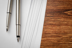 Pens and Sheets on Wooden Table with Copy Space Stock Image