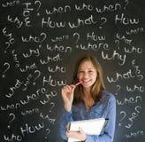 Mujer de negocios de pensamiento con preguntas de la tiza Imágenes de archivo libres de regalías