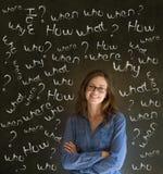 Mujer de negocios de pensamiento con preguntas de la tiza Foto de archivo