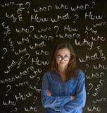 Mujer de negocios de pensamiento con preguntas de la tiza Fotos de archivo