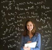 Mujer de negocios de pensamiento con preguntas de la tiza Imagen de archivo libre de regalías