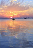 Pensacola Bay Sunset. A sailboat silhouetted against a brilliant sunset in a cove off Pensacola Bay, Florida royalty free stock image