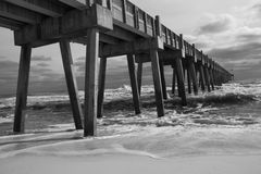 Pensacola Beach Fishing Pier (B&W). Black and white image of heavy surf crashes against the Pensacola Beach fishing pier on Santa Rosa Island, Florida, the Royalty Free Stock Images