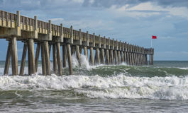 Pensacola Beach Pier as Tropical Storm Hermine Passes. Crashing waves roll ashore at Pensacola Beach fishing pier as tropical hurricane Hermine passes in the Royalty Free Stock Images