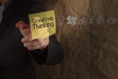 Pensamento criativo do ponto da mão do homem de negócios na nota pegajosa com ico Imagem de Stock