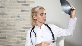 Pensamento da imagem do raio dos examins x do médico geral Doutor fêmea louro bonito em uma clínica de saúde 4K video estoque