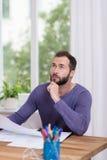 Pensamento de assento do homem em sua mesa Foto de Stock