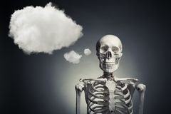 Pensamento de esqueleto humano em um fundo cinzento Imagem de Stock