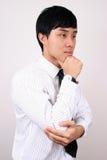 Pensamiento chino joven del hombre de negocios. fotos de archivo libres de regalías