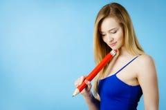 Pensamiento confundido mujer, lápiz grande a disposición Fotografía de archivo libre de regalías