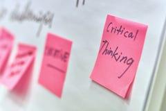 Pensamiento crítico escrito en las etiquetas engomadas de papel rosadas atadas a una carta de tirón fotos de archivo