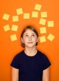 Pensamiento de la chica joven y notas pegajosas Fotos de archivo libres de regalías