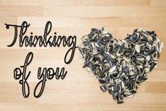 Pensamiento en usted - tarjeta Corazón alineado con las cáscaras de las semillas de girasol en un fondo de la madera de haya fotografía de archivo