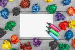 Pensamiento fuera del rectángulo Hojas de papel arrugadas multicoloras y hoja de papel en blanco con las plumas coloridas del fie Imagen de archivo