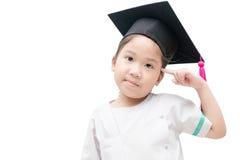Pensamiento graduado del niño asiático de la escuela con el casquillo de la graduación Foto de archivo libre de regalías