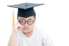 Pensamiento graduado del niño de la escuela con el casquillo de la graduación aislado Imagen de archivo