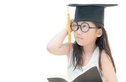 Pensamiento graduado del niño de la escuela con el casquillo de la graduación aislado Fotos de archivo libres de regalías