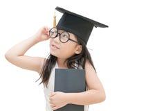 Pensamiento graduado del niño de la escuela con el casquillo de la graduación aislado Fotografía de archivo libre de regalías