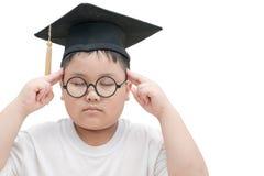 Pensamiento graduado del niño de la escuela con el casquillo de la graduación aislado Fotos de archivo