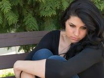 Pensamiento joven y preocupación de la mujer en el banco Fotografía de archivo libre de regalías