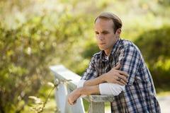 Pensamiento masculino caucásico en el puente de madera Fotografía de archivo