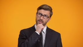 Pensamiento masculino pensativo en las ideas del negocio para el comienzo para arriba, fondo anaranjado metrajes