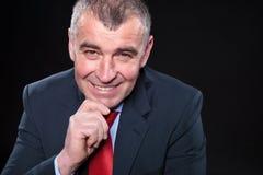 Pensamiento mayor sonriente del hombre de negocios Imagen de archivo